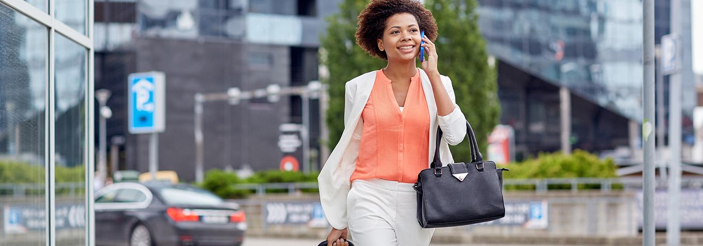 Woman on phone walking down a street